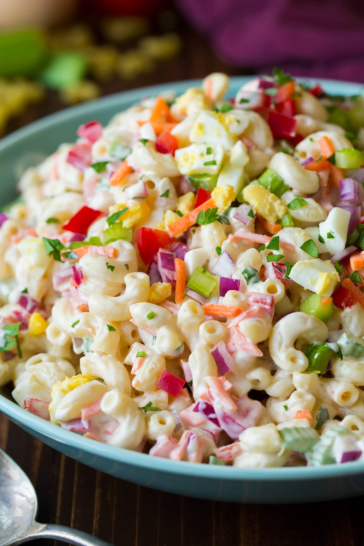 Close up side angle view of macaroni salad in a light blue bowl.