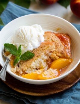 Serving of homemade peach cobbler in a white serving bowl topped with vanilla ice cream and mint.