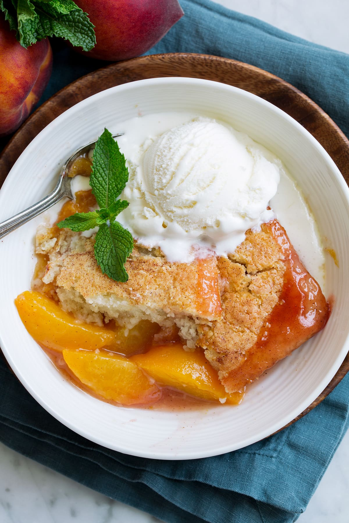 Overhead close up image of peach cobbler showing texture of filling and topping.
