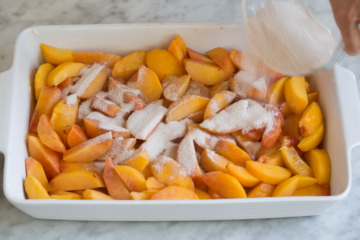 Pouring sugar mixture over peaches in baking dish.