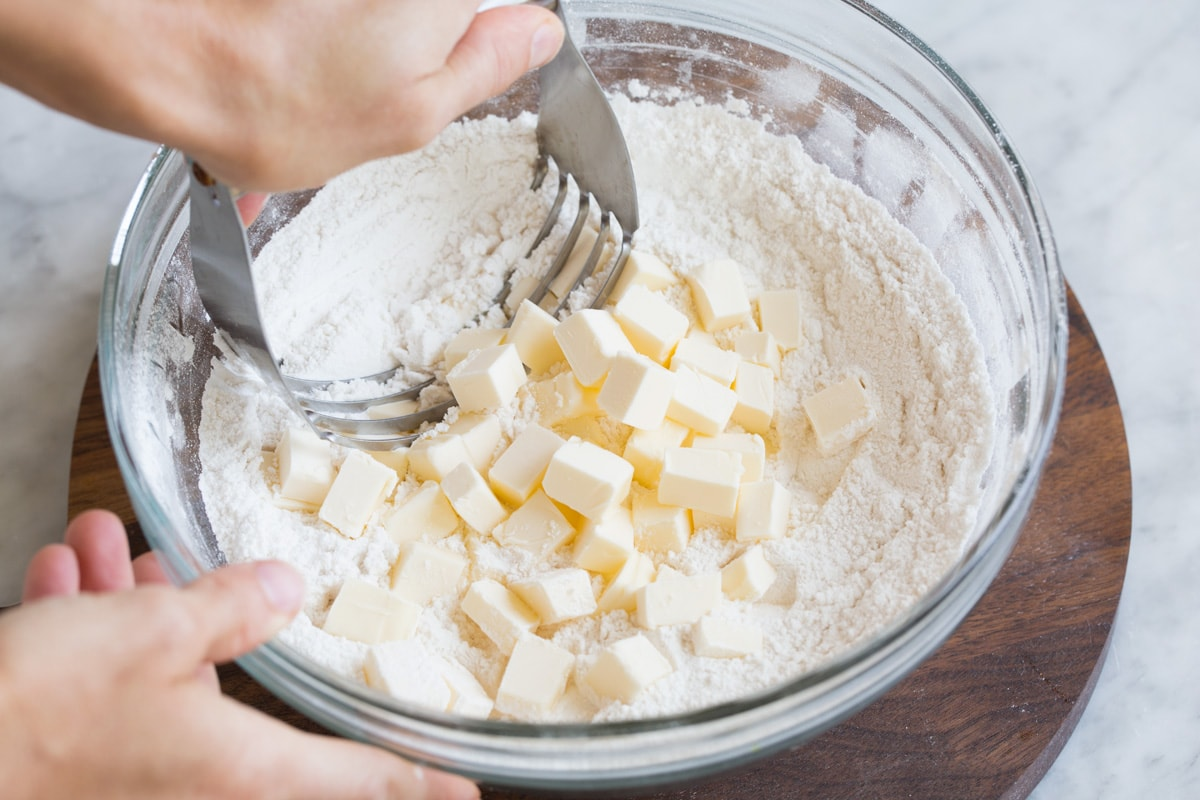 Cutting butter into flour mixture in glass mixing bowl with a pastry cutter.