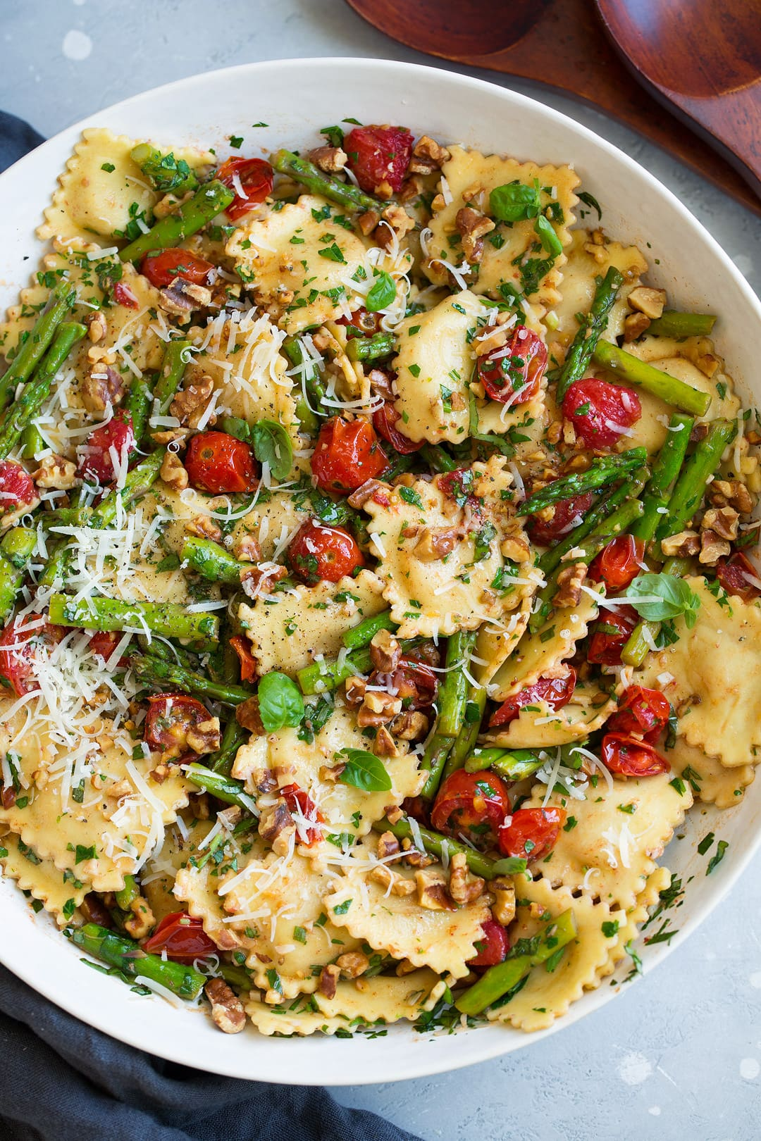 ravioli with tomatoes asparagus walnuts parmesan garlic herbs in serving bowl
