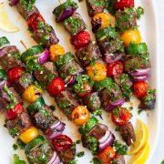 steak kebabs on platter with chimichurri