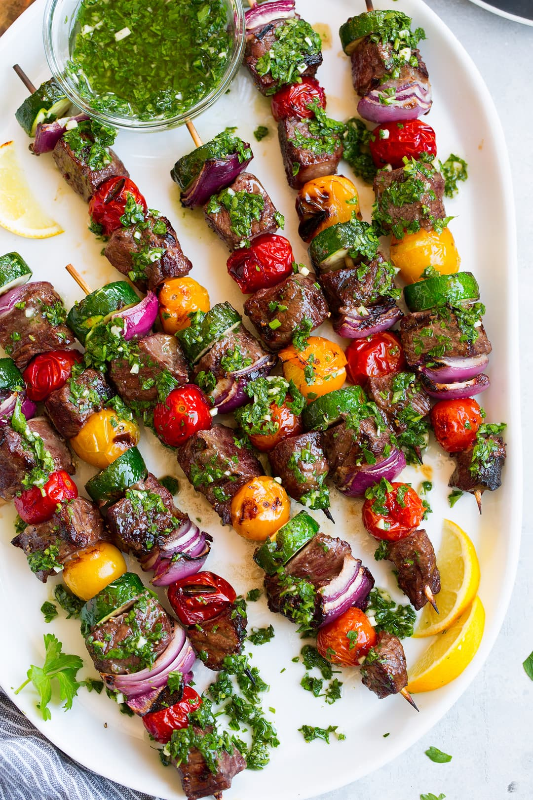 steak kebabs on platter with chimichurri
