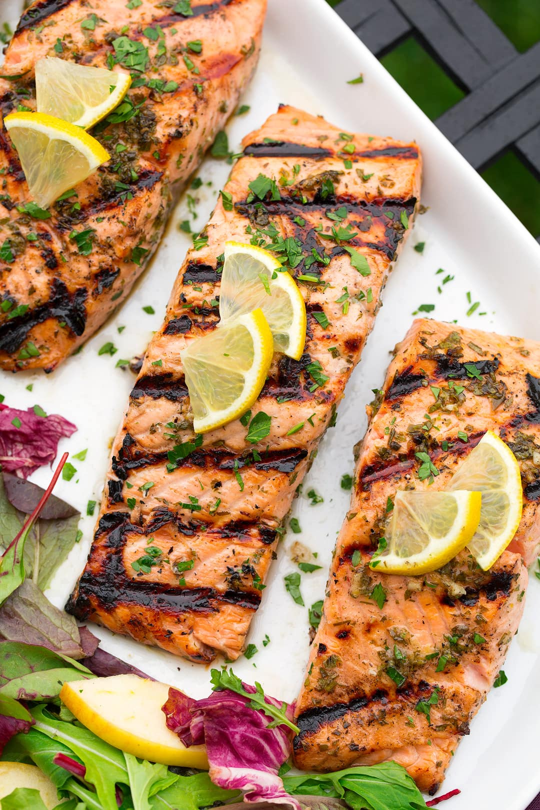 three lemon garlic salmon fillets on white plate