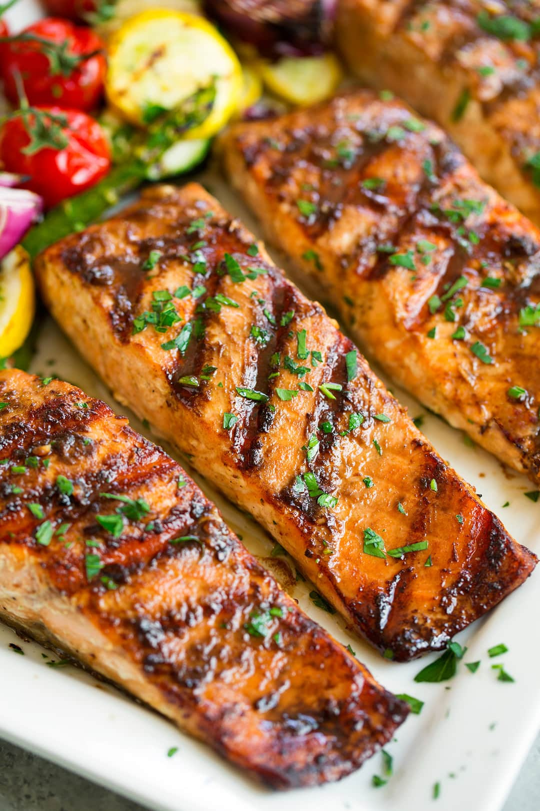 three grilled salmon fillets on white platter