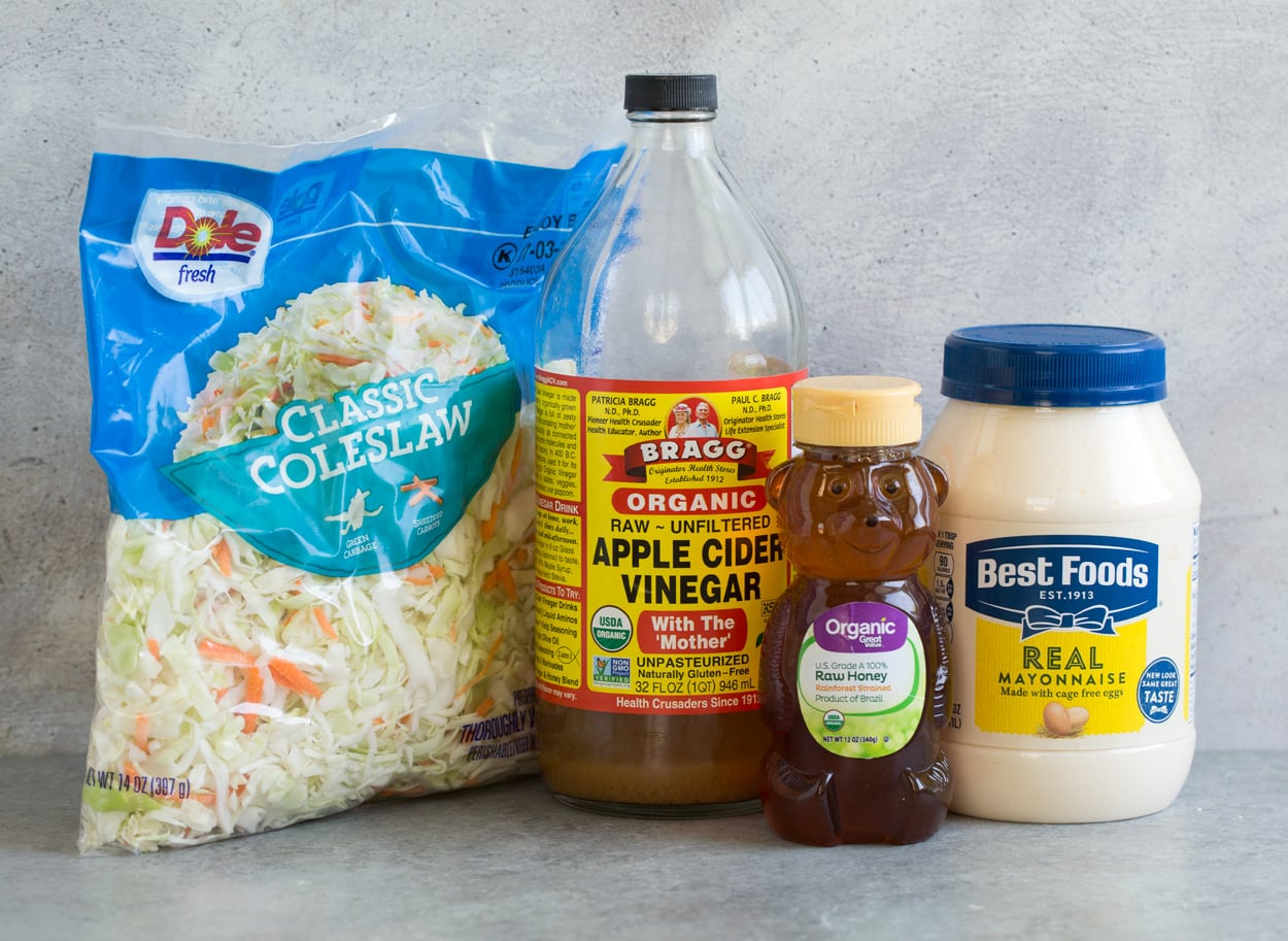 Coleslaw ingredients show here including mayonnaise, honey, apple cider vinegar, and cabbage coleslaw mix.