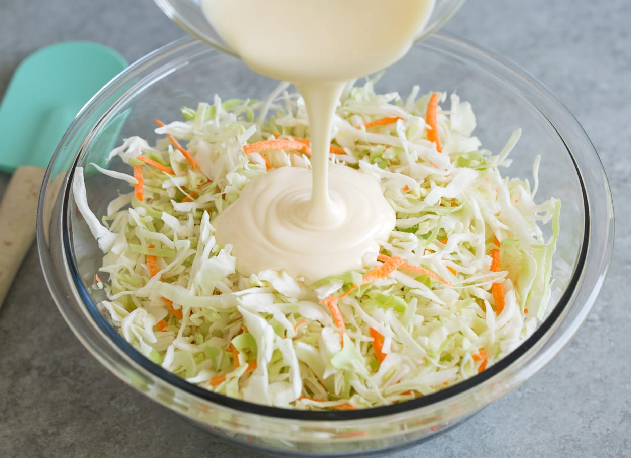 Adding coleslaw dressing to coleslaw in mixing bowl.