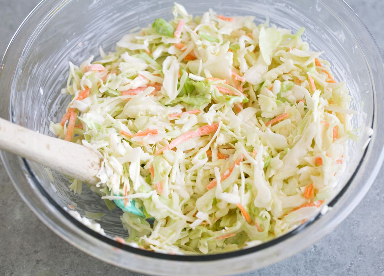 Tossing coleslaw mixture and dressing in mixing bowl