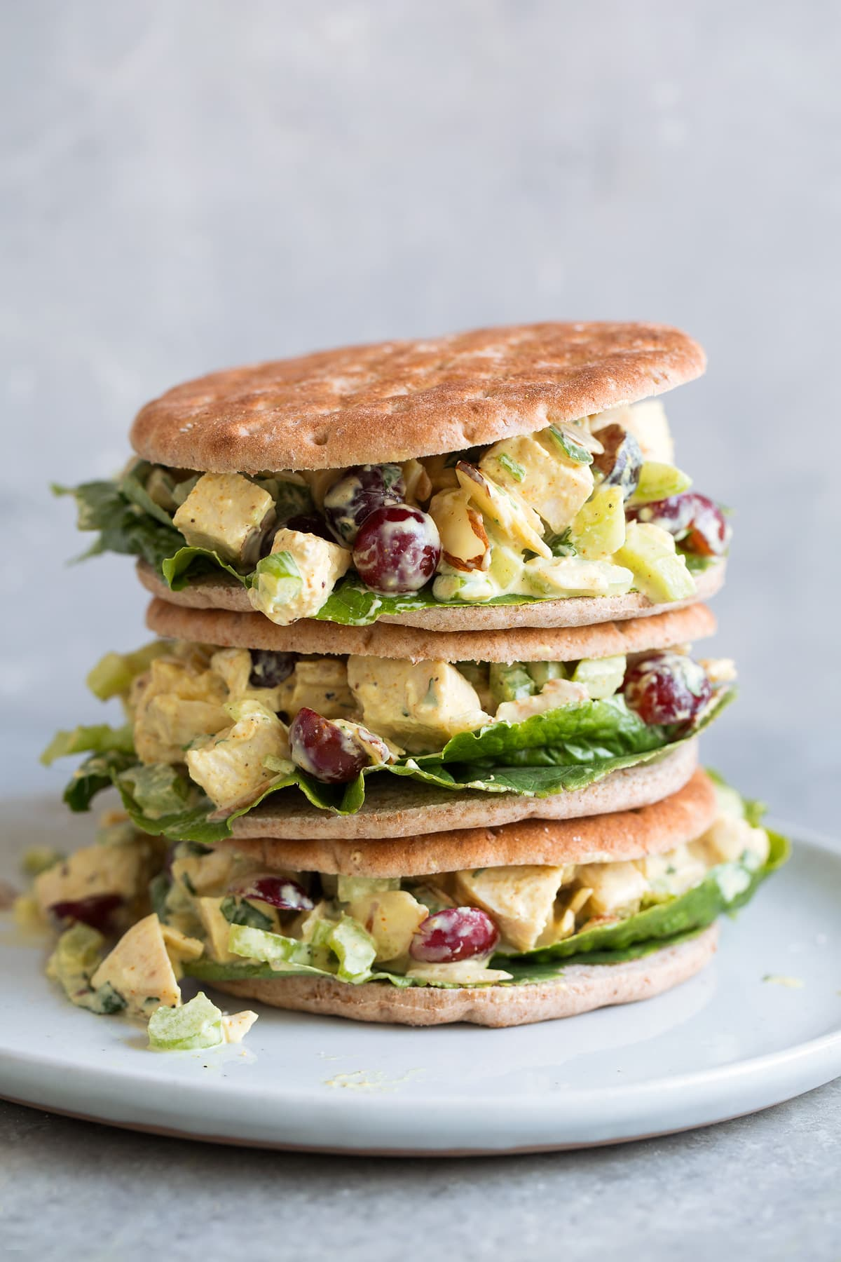 Curry Chicken Salad sandwiches stacked on a white plate
