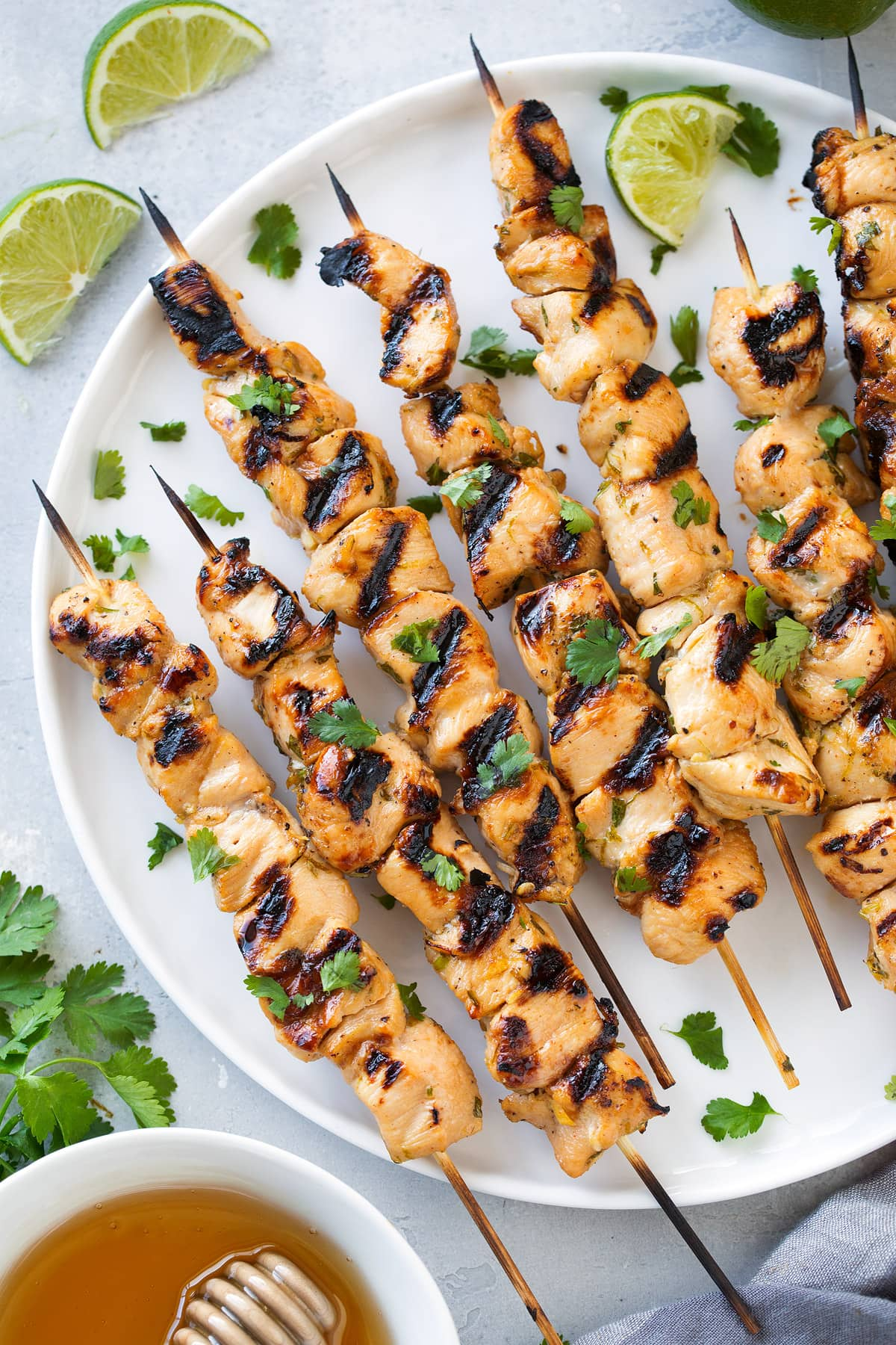 honey lime chicken skewers on white plate with lime wedges