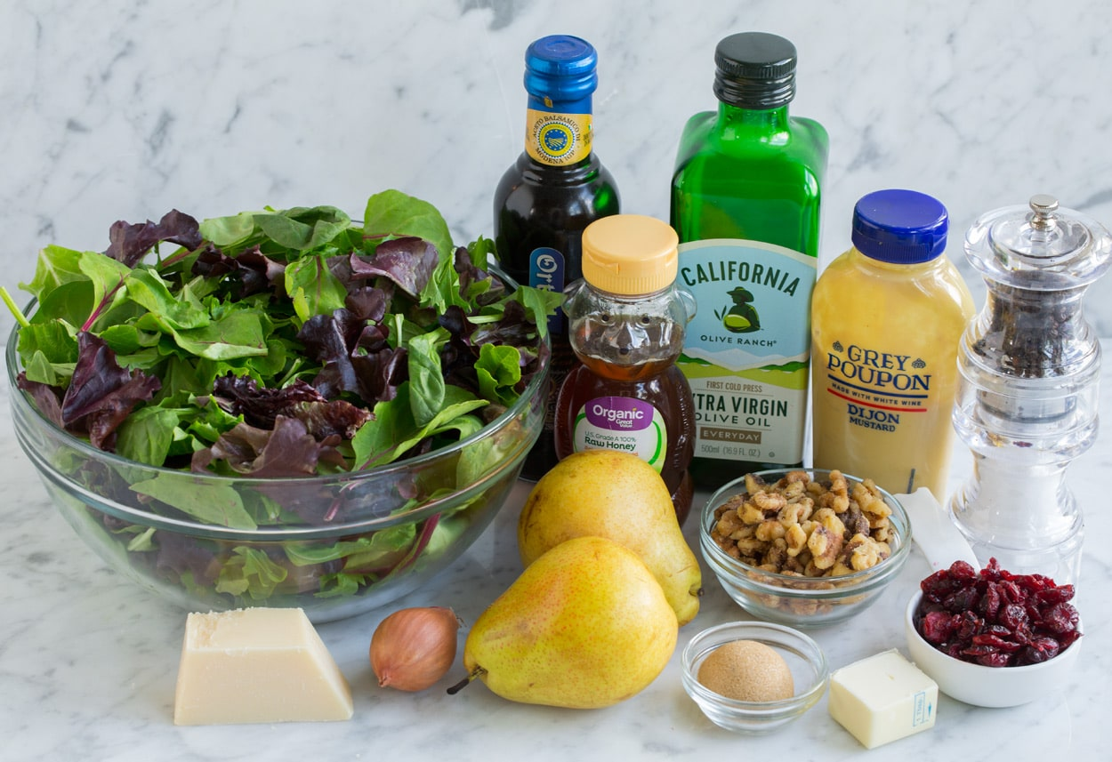 Ingredients for pear salad sitting on marble surface. Includes spring greens, pears, parmesan, olive oil, balsamic vinegar, butter, pecans, cranberries, mustard, honey, brown sugar.