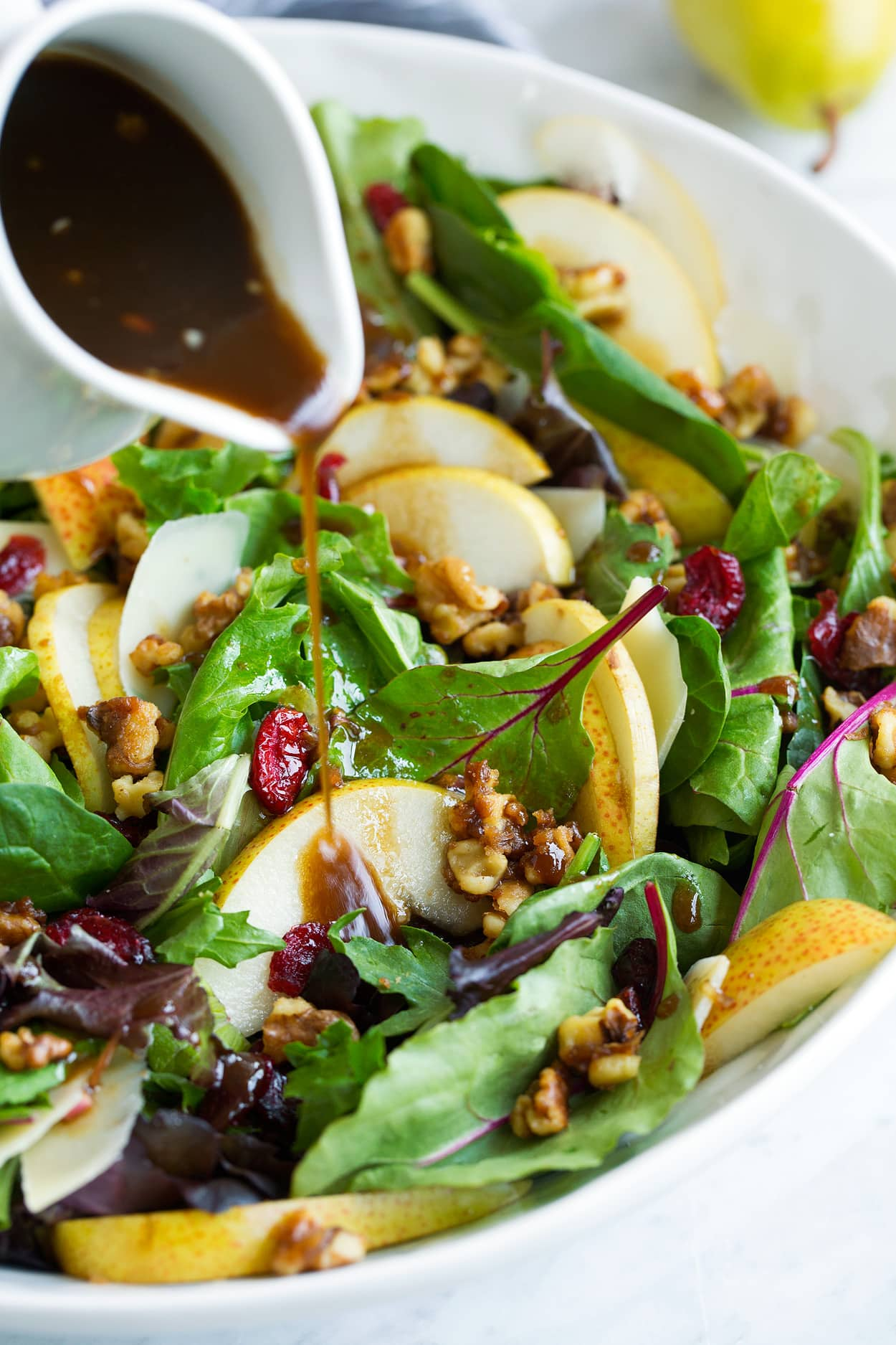 Pouring Balsamic Vinaigrette over Pear Salad in Salad Bowl