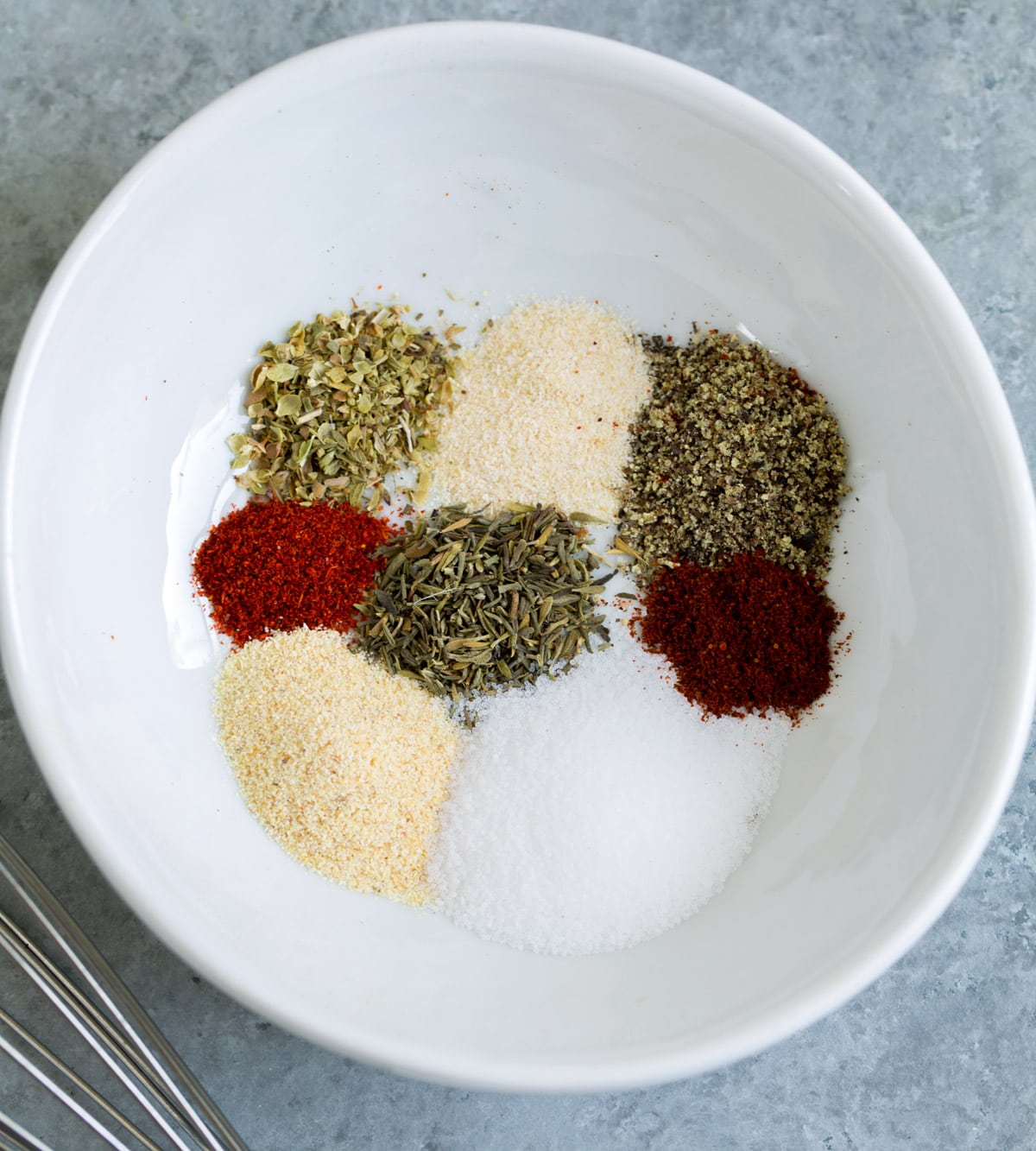 Spices in a mixing bowl to season baked chicken.