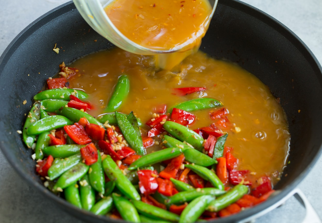 Orange Garlic Shrimp adding orange stir fry sauce to skillet along with veggies