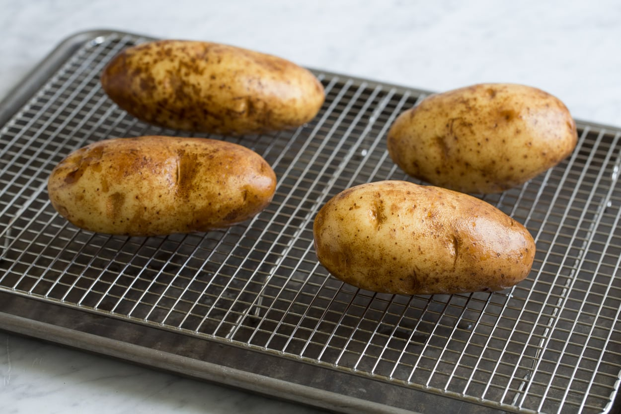 Baked Potatoes shown here set on a wire rack over a baking sheet before baking