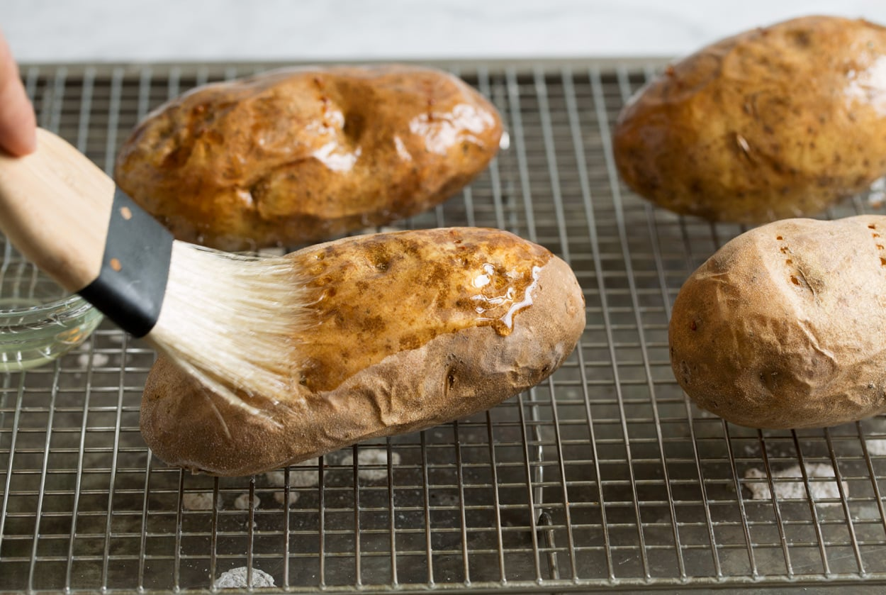 Baked Potatoes shown here brushing with vegetable oil