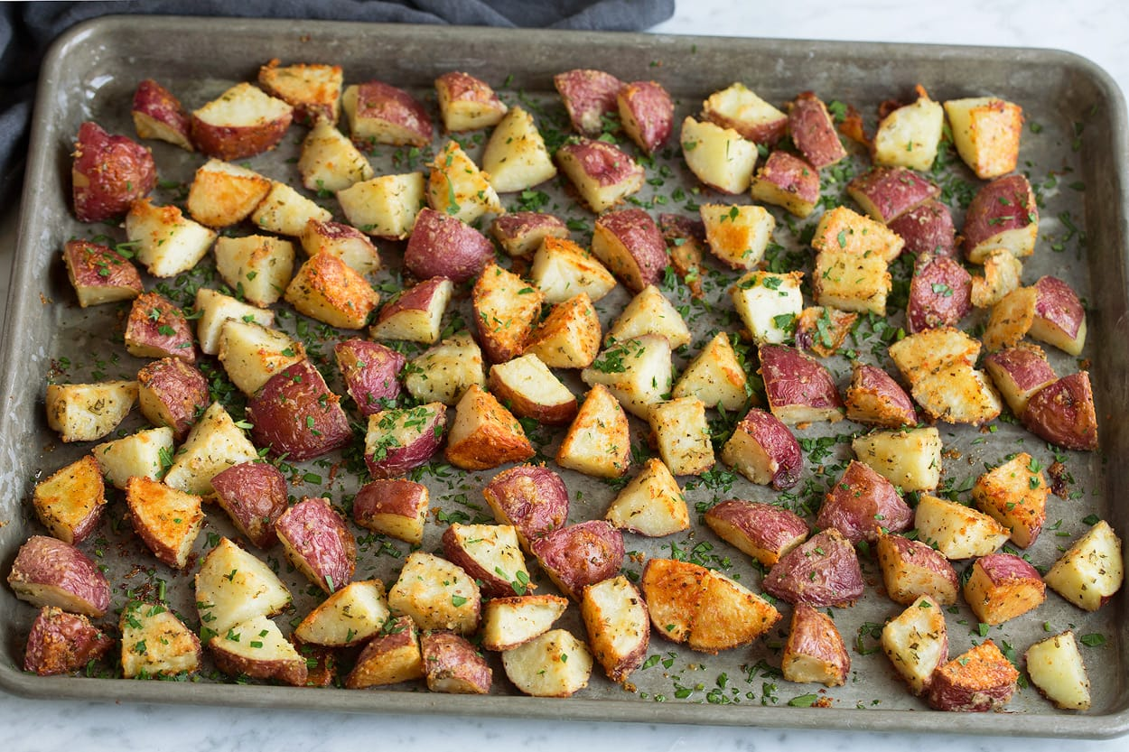 Potatoes on baking dish after roasting in oven showing their golden brown color.