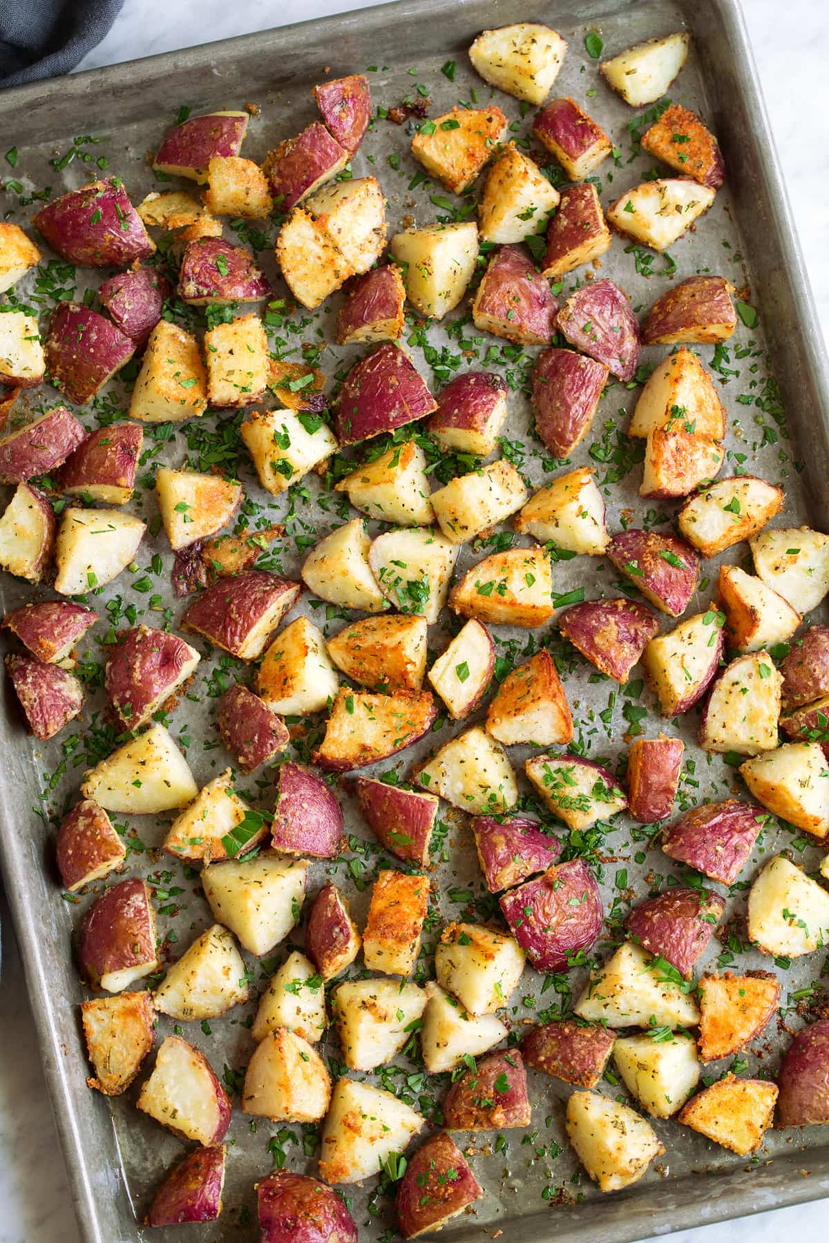 Overhead image of roasted red potatoes spread across baking sheet.