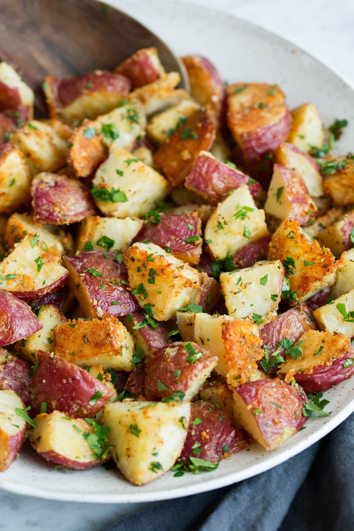 Roasted Potatoes with a parmesan crust and fresh parsley in a serving bowl.