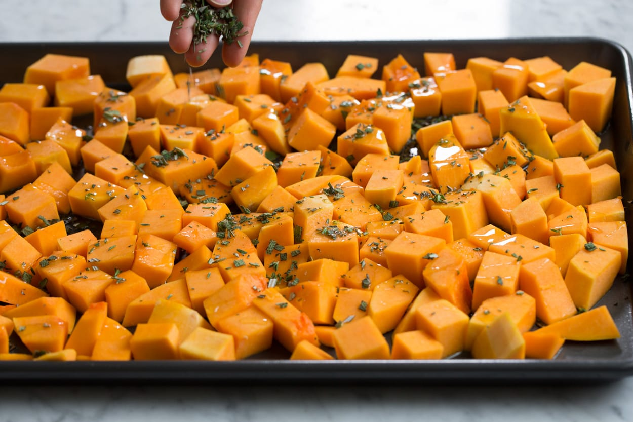 Drizzling butternut squash on a baking sheet with olive oil and sprinkling with herbs.