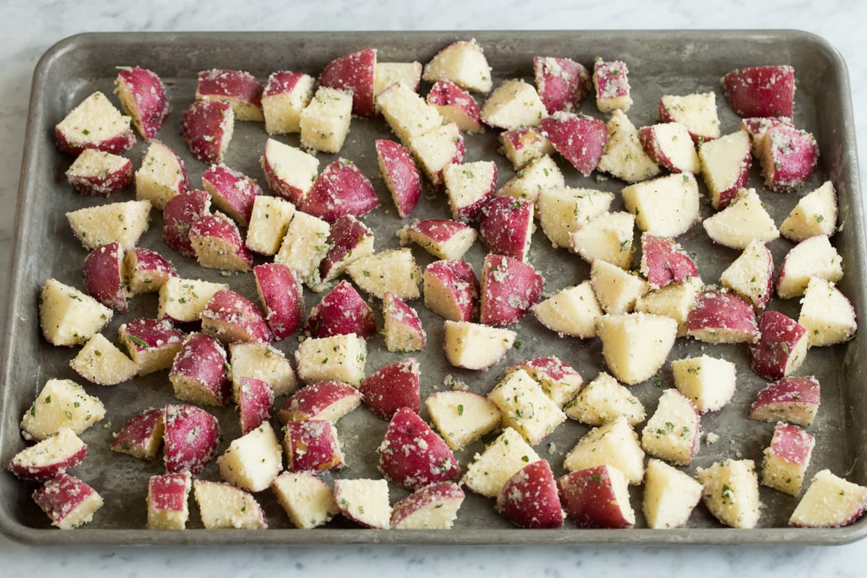 Potato cubes tossed with parmesan on a baking sheet to roast.