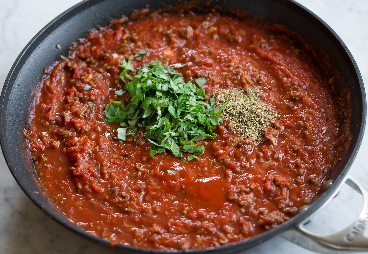 Adding basil and oregano to beefy tomato spaghetti sauce in pan.