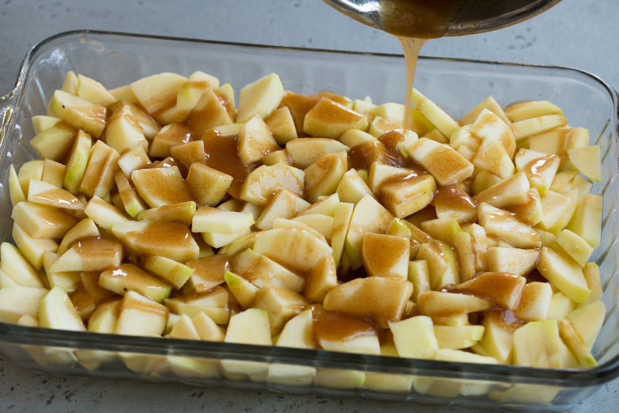 apple cobbler shown here pouring sugar mixture over apples in baking dish