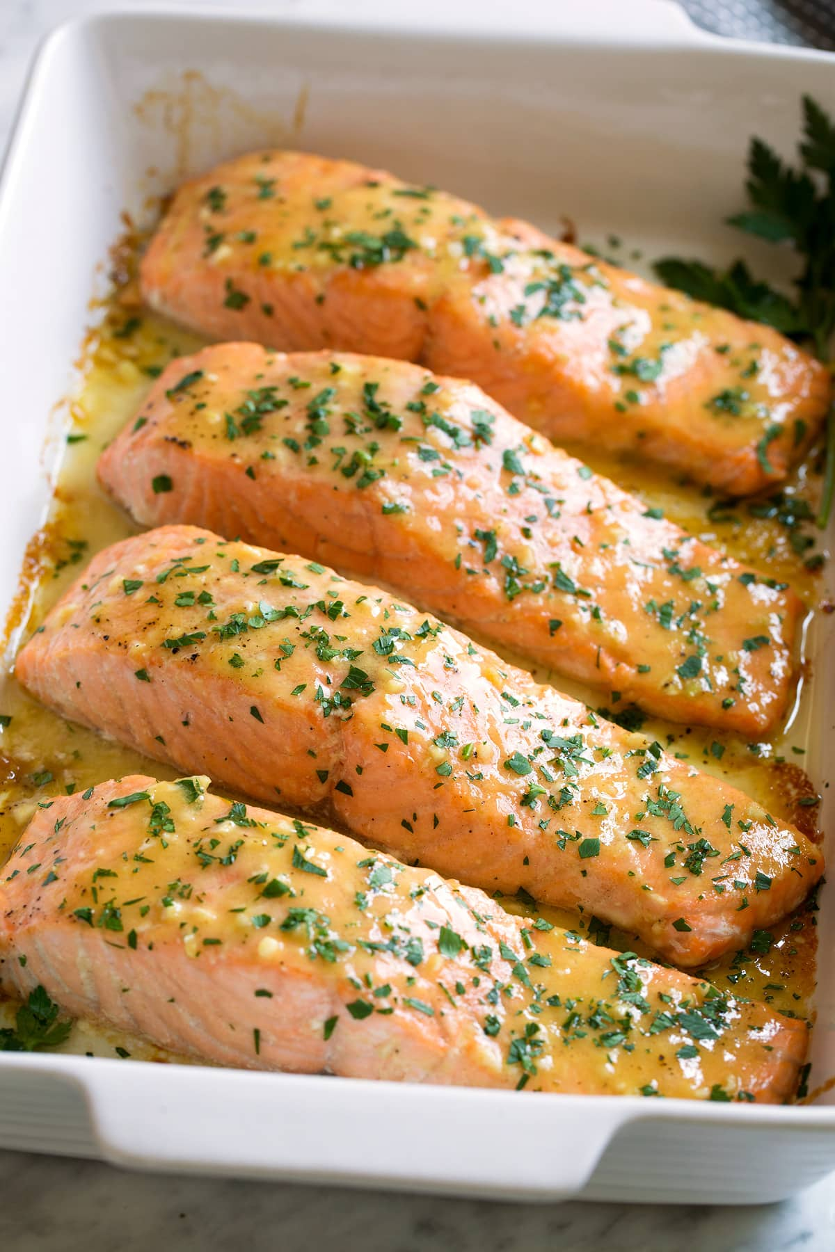 Four salmon fillets in a baking dish brushed with a sweet and tangy, buttery honey mustard sauce.