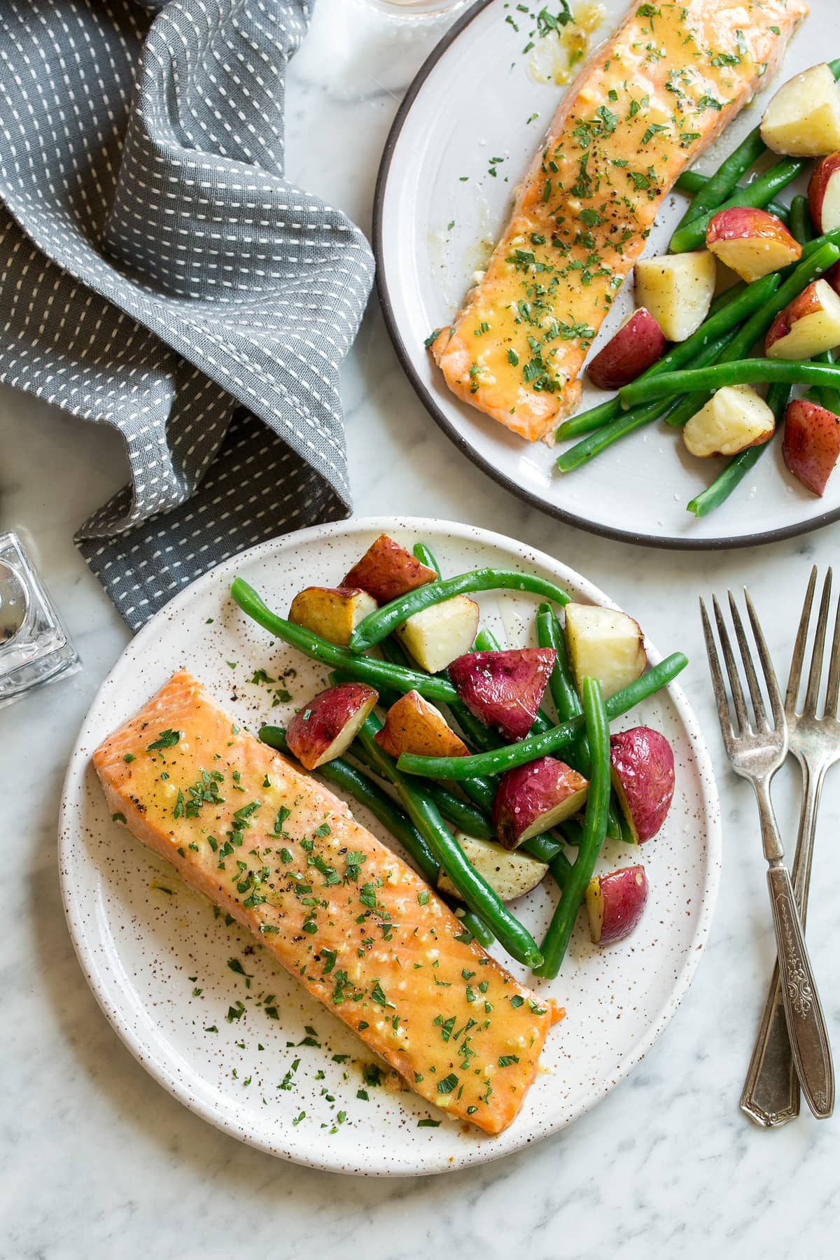 Overhead image of two servings of Baked Salmon with Buttery Honey Mustard Sauce on white serving plates set over a marble surface.