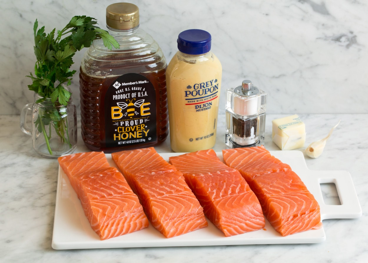Ingredients for baked salmon shown here. Salmon fillets honey dijon mustard garlic salt pepper parsley.