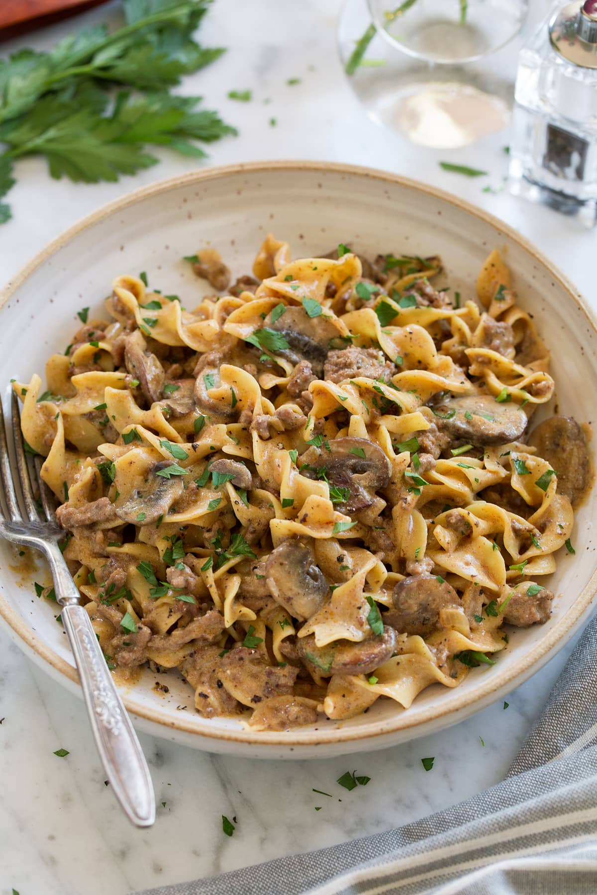 One Pot Easy Beef Stroganoff shown in a cream pasta bowl with a fork to the side. Bowl is sitting on a marble surface, parsley and a salt shaker are in the background.