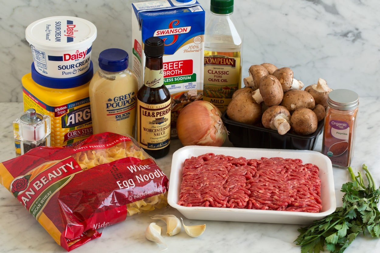Beef Stroganoff ingredients shown here. Olive oil, mushrooms, yellow onion, garlic, lean ground beef, paprika, beef broth, dijon mustard, Worcestershire, dry egg noodles, cornstarch, sour cream