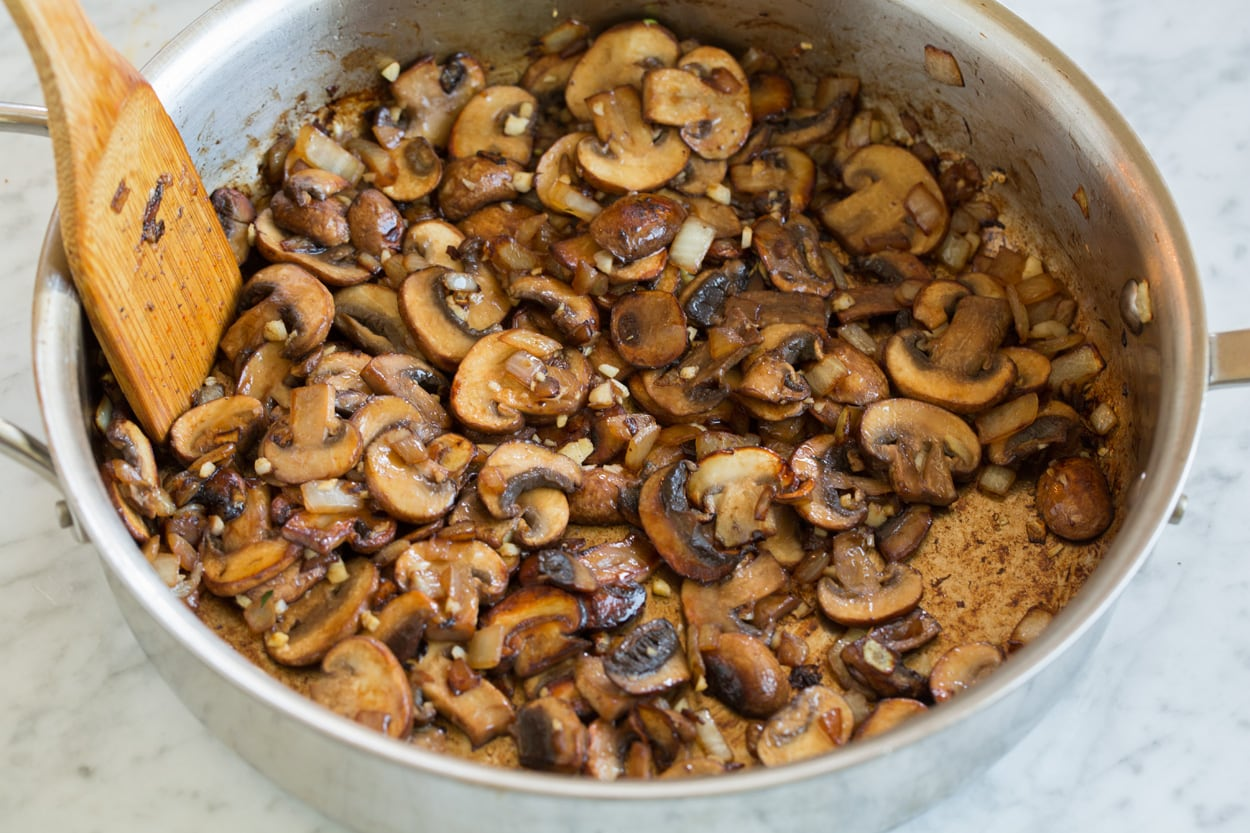 Sauteeing mushrooms and onions in a saute pan for beef stroganoff