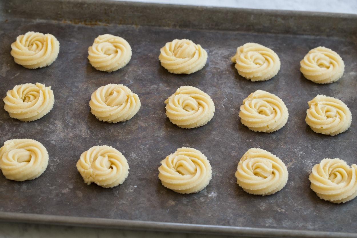 Butter cookies before baking on a baking sheet.