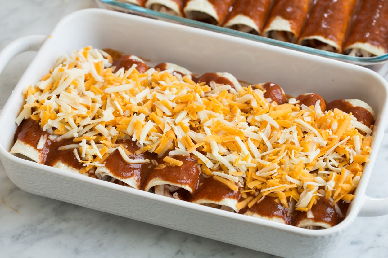 Chicken enchiladas in baking dish with cheese and sauce on top before baking