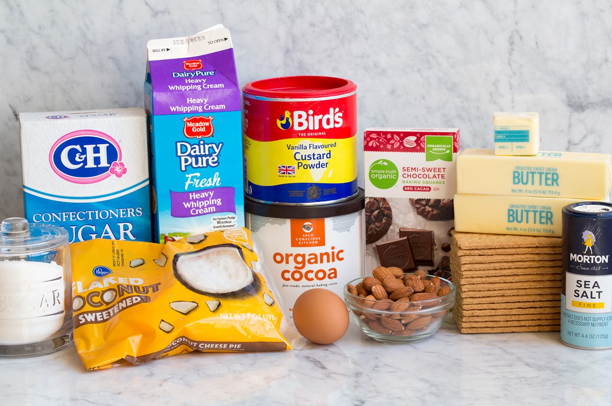 Image of ingredients used to make Nanaimo Bars. Includes sugar, coconut, powdered sugar, cream, custard powder, cocoa powder, egg, almonds, chocolate, graham crackers, butter, and salt.
