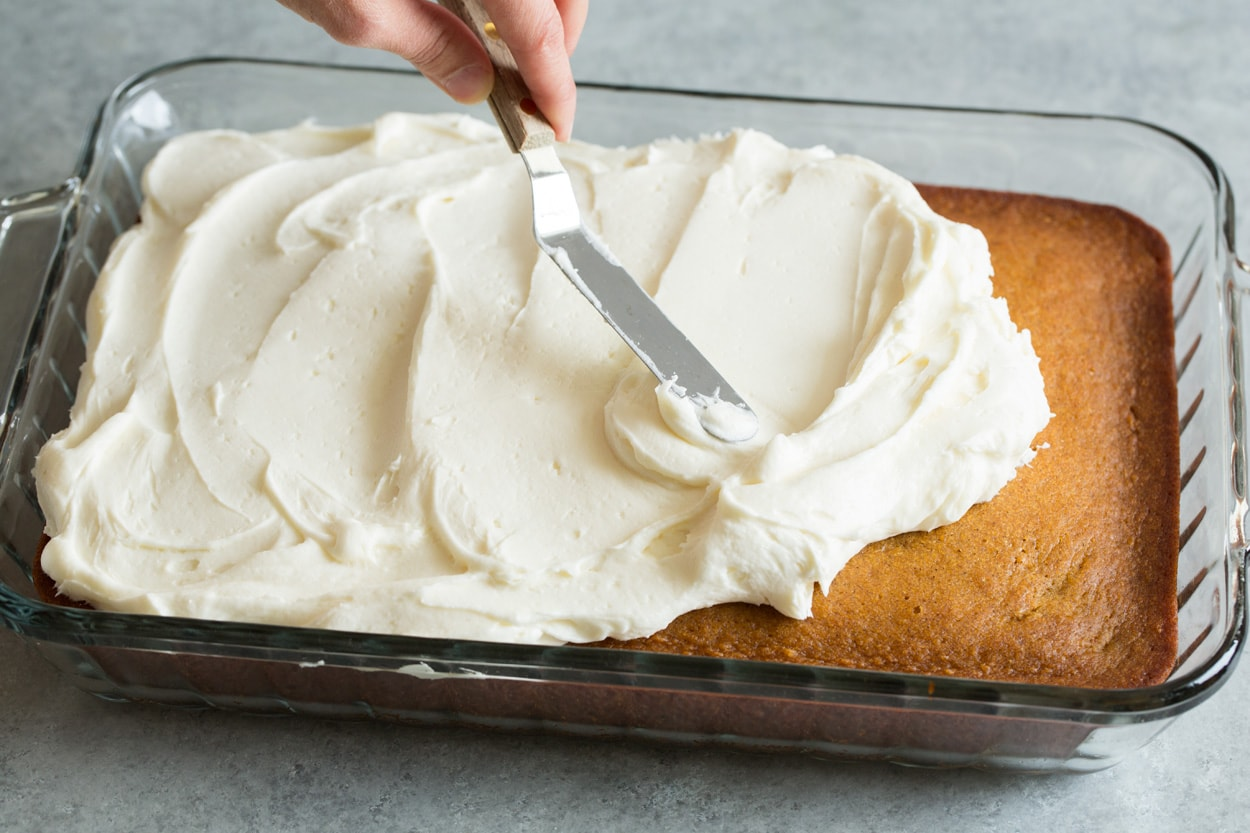 Pumpkin Cake shown here spreading cream cheese frosting onto pumpkin cake