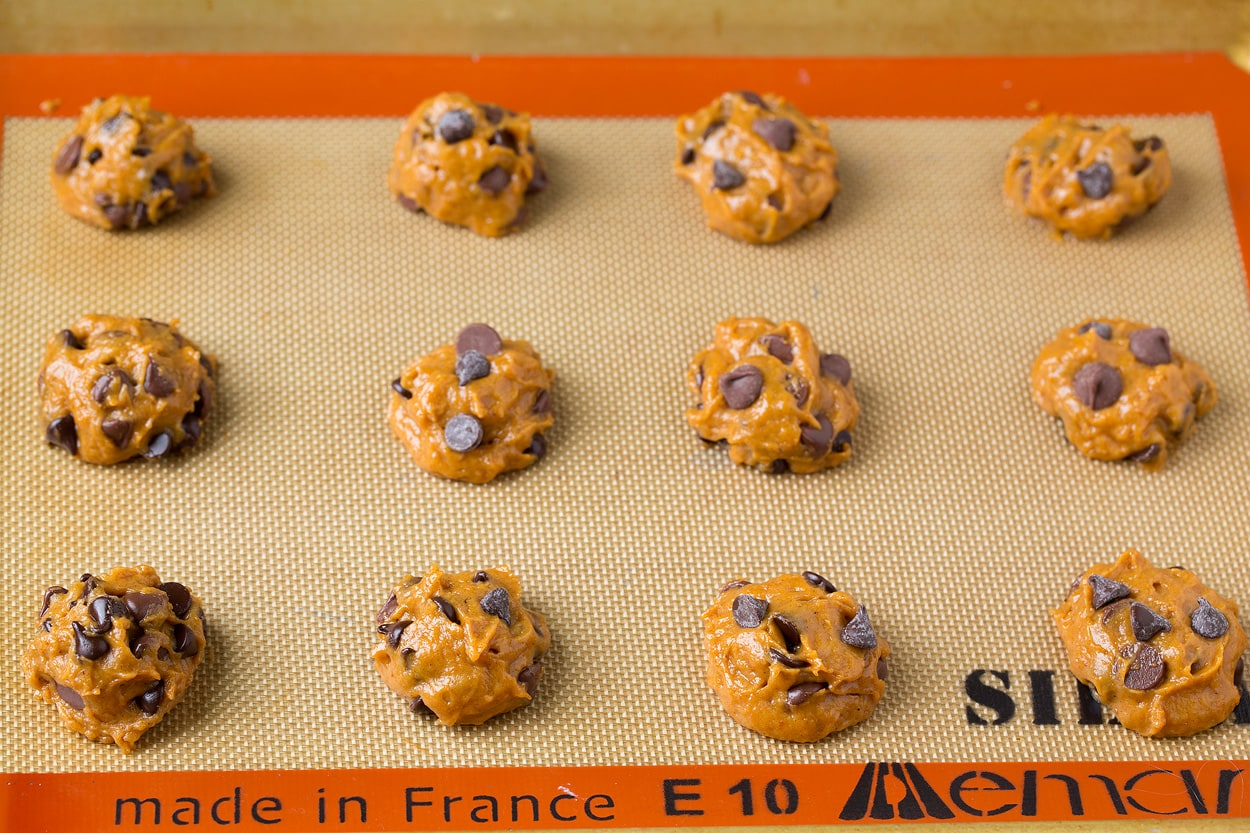 Twelve pumpkin chocolate chip cookie dough balls on baking sheet before baking.