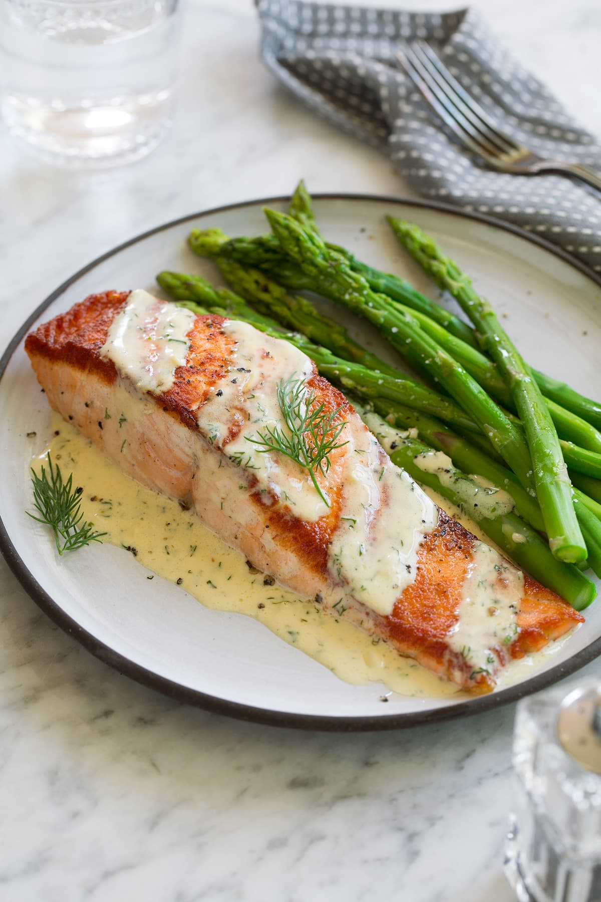 Salmon fillet on a white plate set over a marble surface. Topped with dijon sauce and served with a side of asparagus.