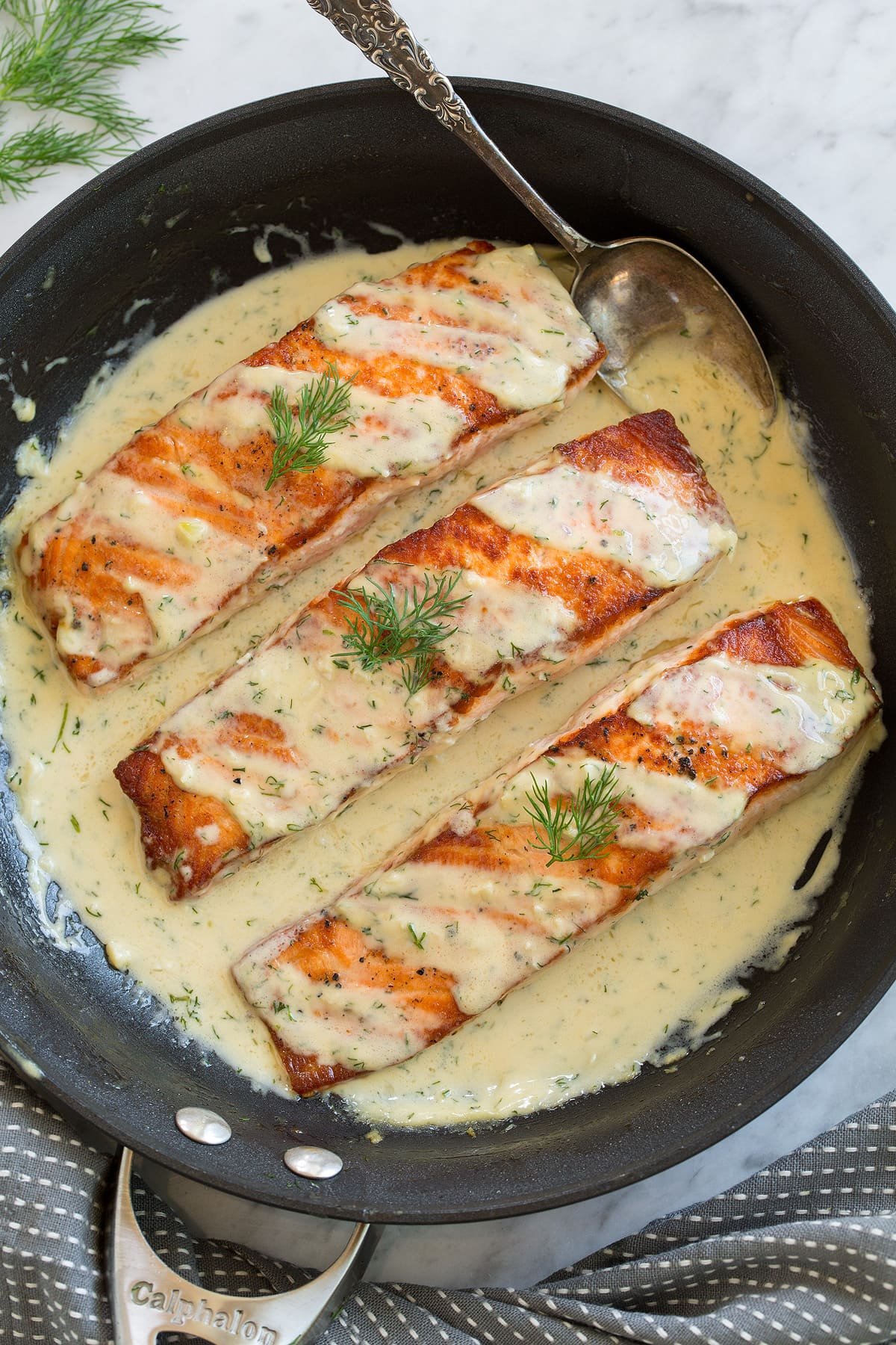 Three salmon fillets in a skillet with a creamy dijon sauce.