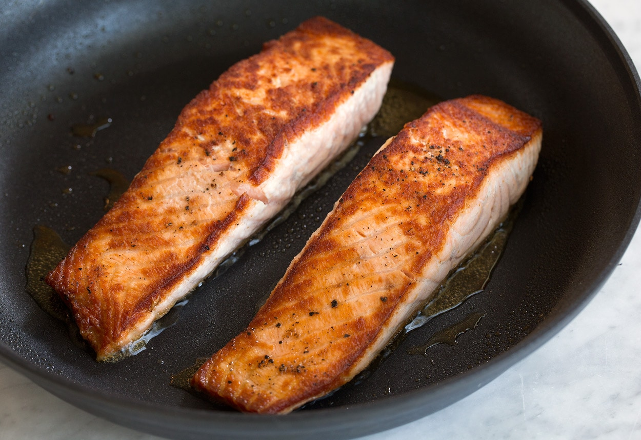 Two golden brown pan seared salmon fillets shown here in large non-stick skillet.