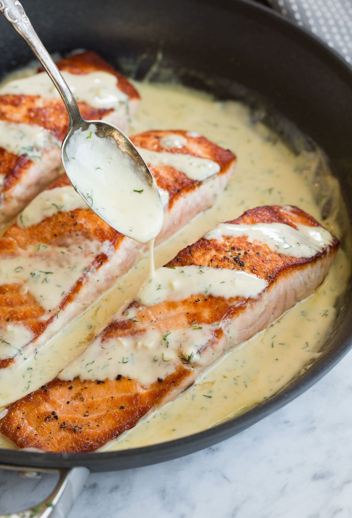 Spooning sauce over a fillet of salmon in a skillet.