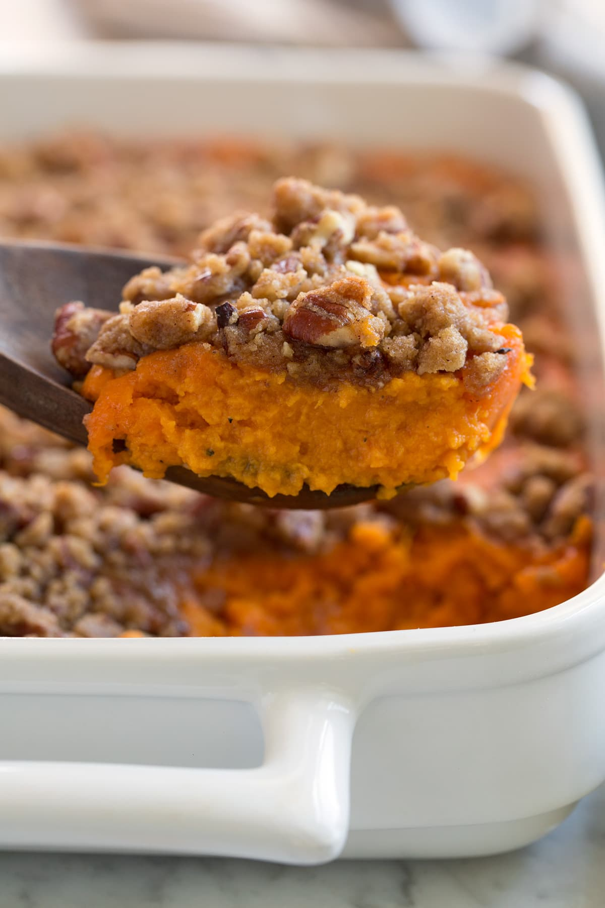 Close up image of a scoop of sweet potato casserole showing creamy orange sweet potato layer and a crisp, sugary pecan crumble.