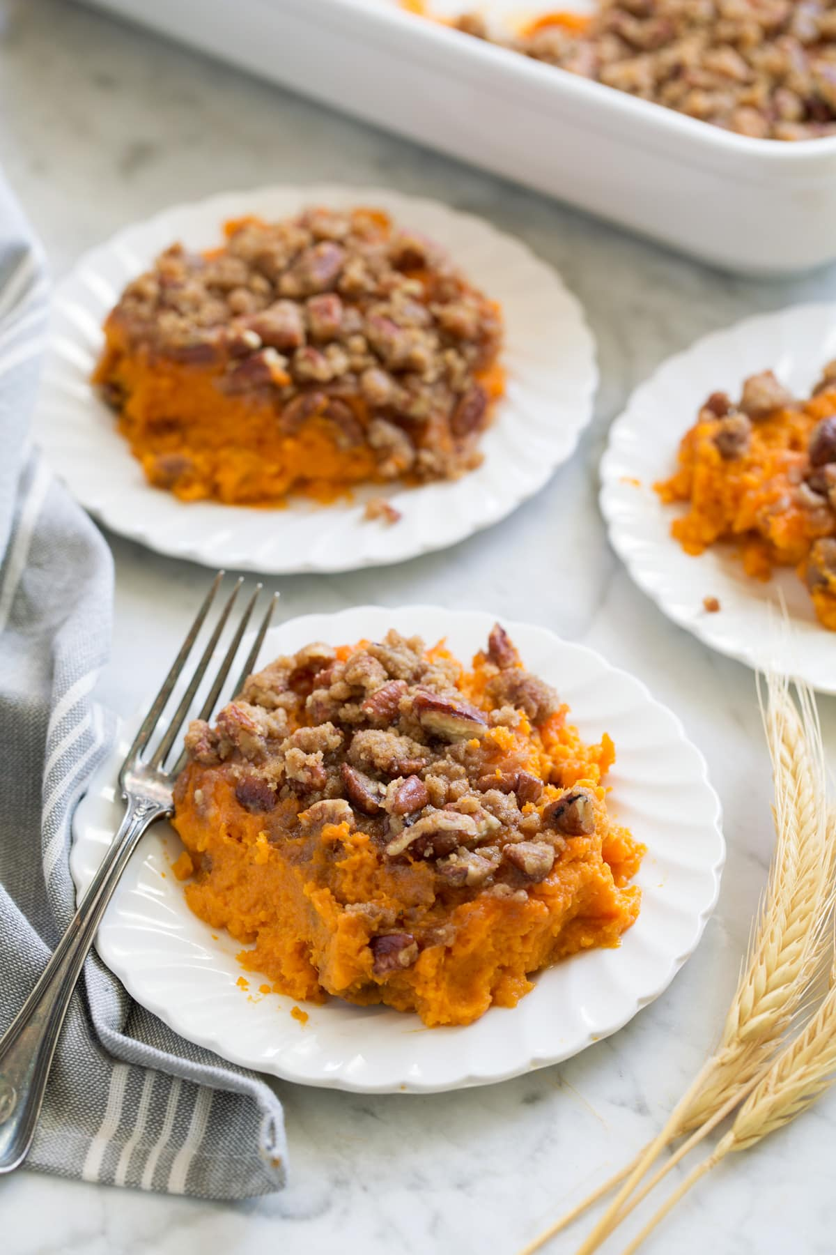 Sweet Potato Casserole shown in three individual servings and small white scalloped plates set over a marble surface.