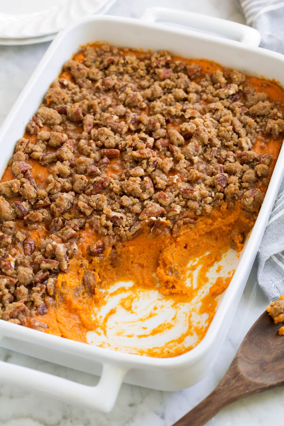 Sweet Potato Casserole with a cinnamon pecan crumble on top, served in a white casserole dish.