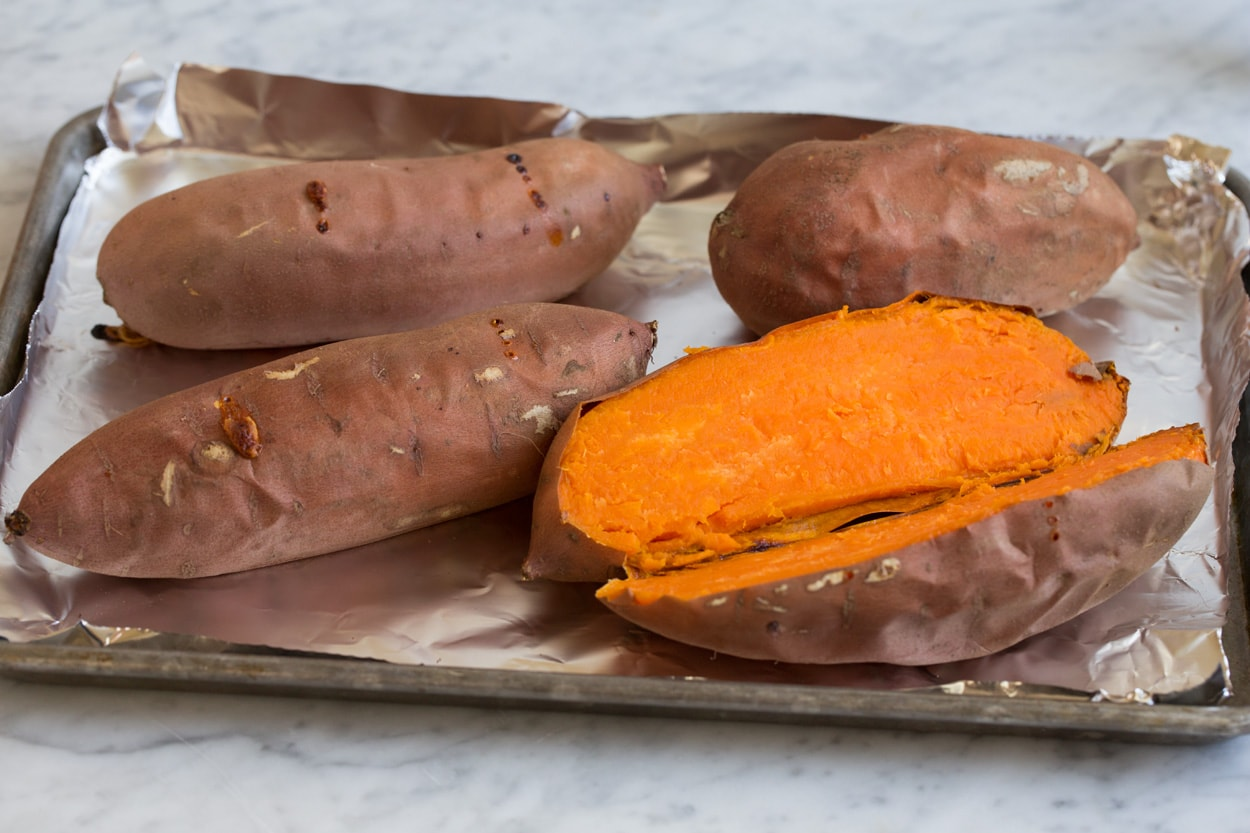 Four baked sweet potatoes shown here, one sliced open. Before adding to sweet potato casserole.