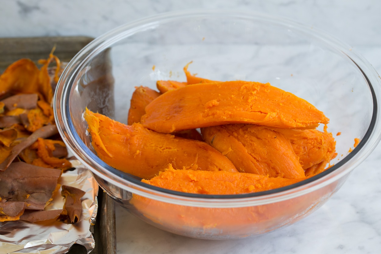 Sweet potatoes in a large glass mixing bowl to make sweet potato casserole.