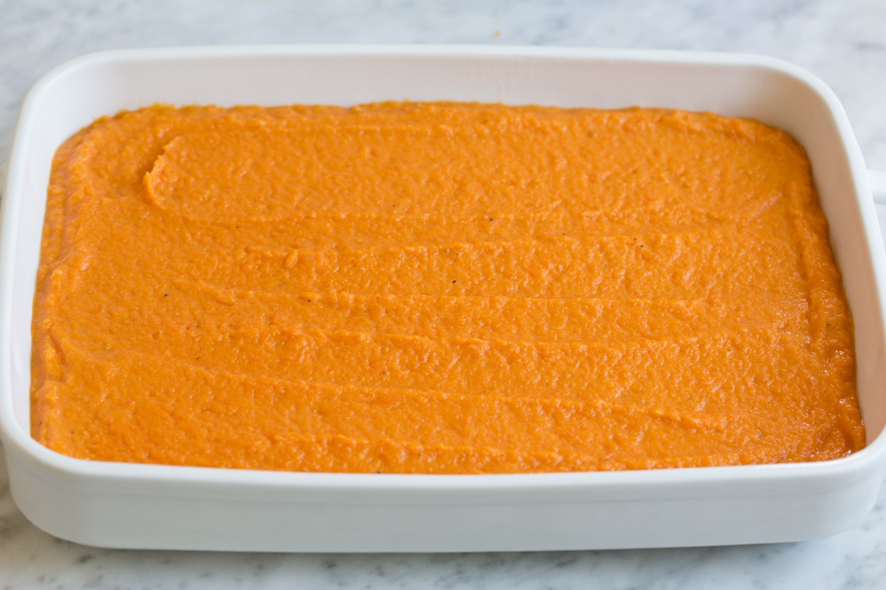 Sweet potato layer spread into white ceramic baking dish for sweet potato casserole.