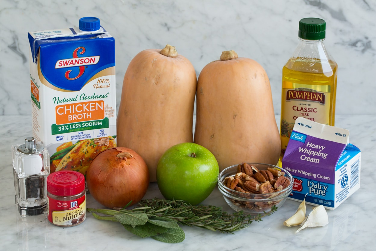 Ingredients for Butternut Squash Soup shown here squash chicken broth apples olive oil onion garlic cream nutmeg herbs pecans